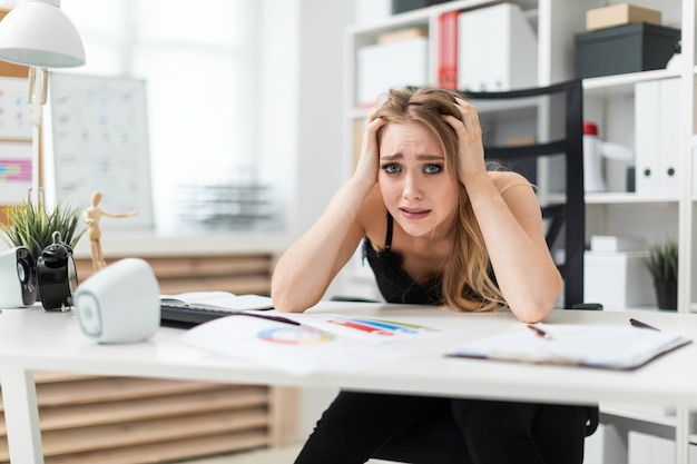 若い女の子がオフィスのテーブルに座っていると彼女の頭の後ろに彼女の手を握っています
