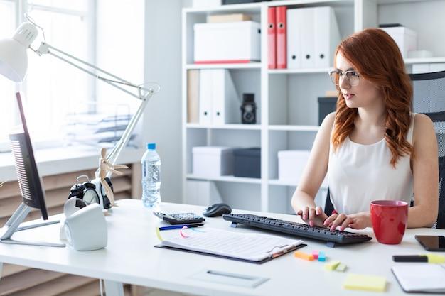 Красивая молодая девушка сидит на столе в офисе и набрав на клавиатуре.