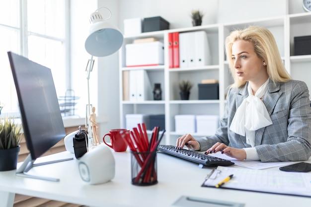 コンピューターとドキュメントを扱うオフィスの少女。
