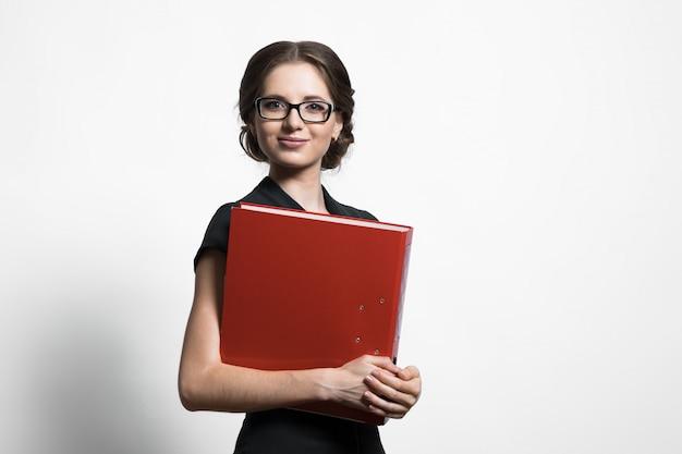 Портрет уверенно красивая молодая бизнес-леди держа связыватель в ее руках стоя на сером цвете