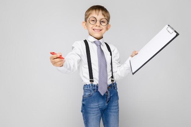 白いシャツ、サスペンダー、ネクタイ、軽いジーンズを着た魅力的な少年が灰色の上に立っています。少年はペンとメモ用のシートを持っています