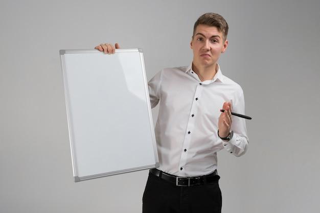 きれいな磁気ボードと彼の手の分離白マーカーで若い男の肖像