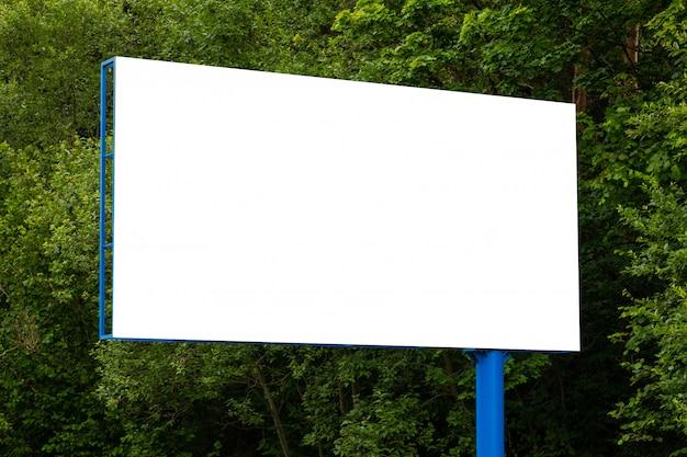 Макро белый пустой рекламный щит против зеленого леса вдоль дороги