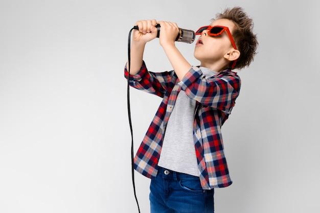 Красивый мальчик в клетчатой рубашке, серой рубашке и джинсах стоит на сером