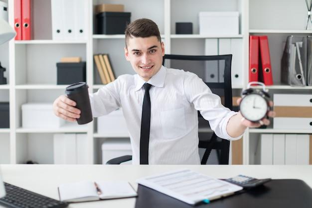 オフィスのテーブルに座って、コーヒーと目覚まし時計を保持している若い男。被写界深度の写真は、ガラスと目覚まし時計に焦点を当てています。