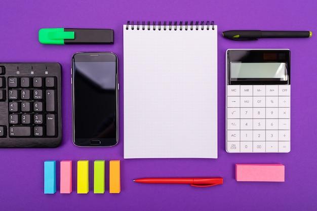電卓、スマートフォン、カラフルな背景にノートブックでモダンなワークスペース。上面図。