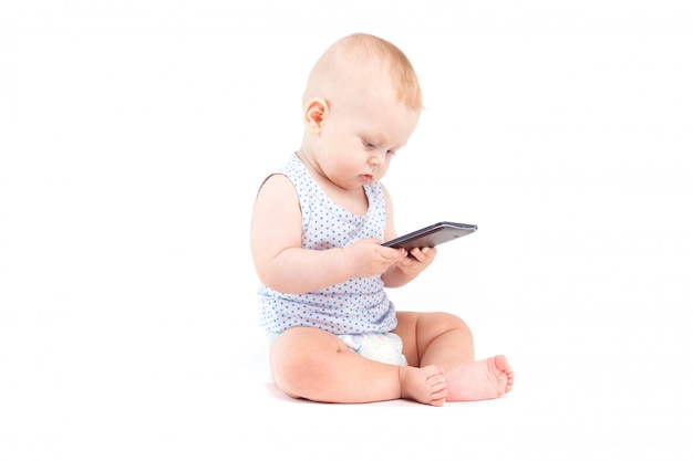 青いシャツとおむつでかわいいかわいい男の子は携帯電話を保持します。
