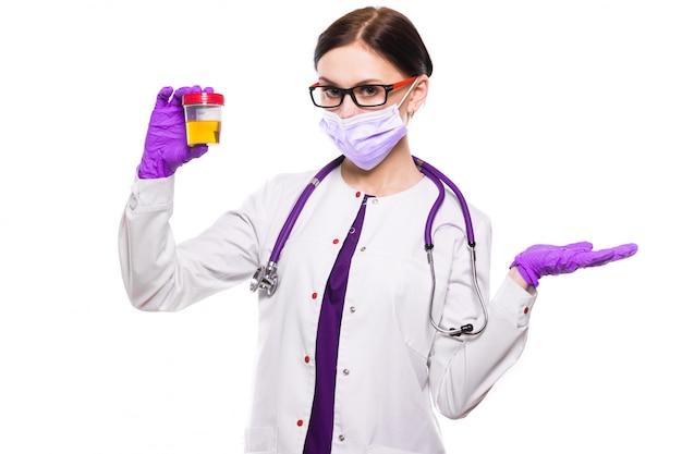 Молодой красивый женский доктор держа образец мочи в ее руках в медицинской маске и стерильных перчатках