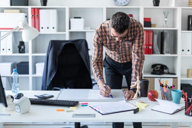 事務所の男がテーブルの近くに立っていて、磁気ボードにマーカーを描画します