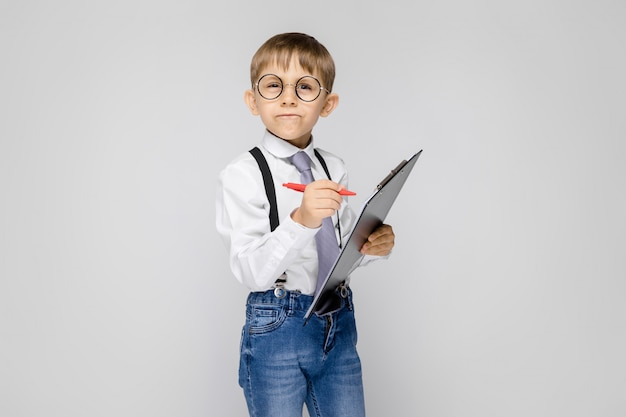 白いシャツ、サスペンダー、ネクタイとライトジーンズの魅力的な男の子がグレーに立っています