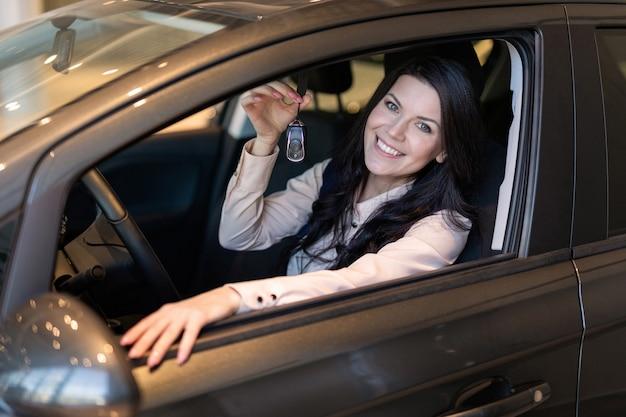 幸せな女性のバイヤーは、ディーラーで彼女の新しい車を調べます