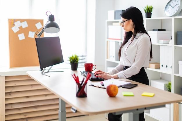 若い女の子がテーブルの近くに立っているとキーボードでテキストを入力しています。