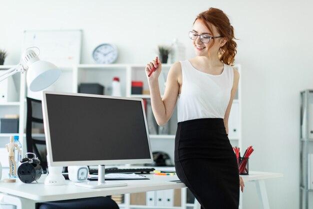オフィスの美しい若い女性がテーブルに座り、赤鉛筆を手に持っていました。