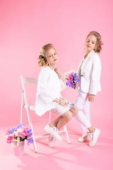 ピンクの背景の椅子に近いポーズの花の花束と軽い服の女の子を双子に。