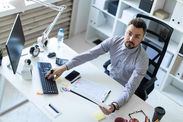 オフィスの若い男がテーブルに座って、手にマーカーを持ち、ドキュメントとコンピューターを操作します。