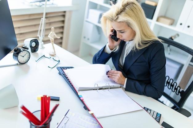 Молодая женщина сидит за столом в офисе, разговаривает по телефону и глядя на документы.
