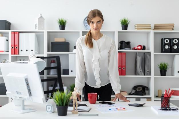 若い女性がオフィスのテーブルのすぐ横に立っています。
