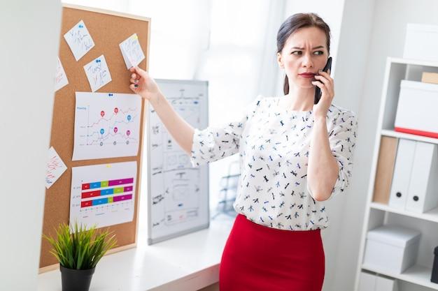 ステッカーとボードの近くのオフィスに立って、電話で話している若い女性。
