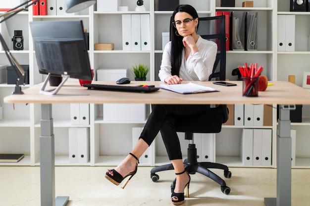 若い女性がコンピューターの机に座っています。女性の横に文書とマーカーがあります。