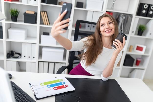 オフィスのテーブルに座って、コーヒーと電話を保持している若い女性。