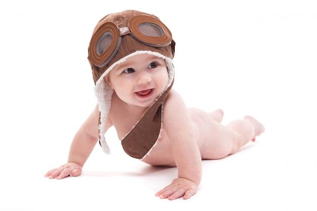パイロットの帽子で裸のかわいい笑顔の赤ちゃんが飛んでいます