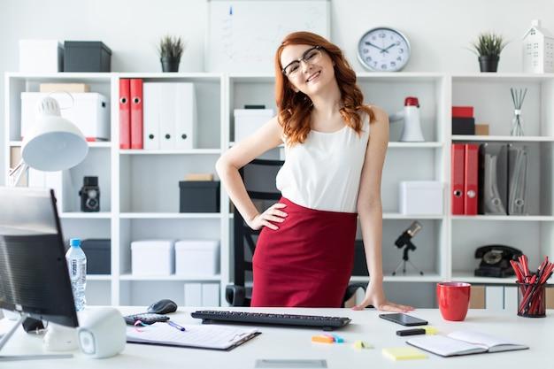 Красивая молодая девушка стоит в офисе возле стола. девушка положила руку на бедро, а вторая наклонилась к столу.