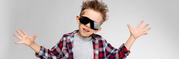 格子縞のシャツ、灰色のシャツ、ジーンズを着たハンサムな男の子が灰色に立ちます。黒いサングラスの少年。少年は両手を横に広げた。
