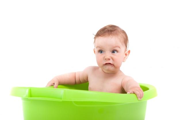 かわいい小さな男の子は緑の浴槽でお風呂