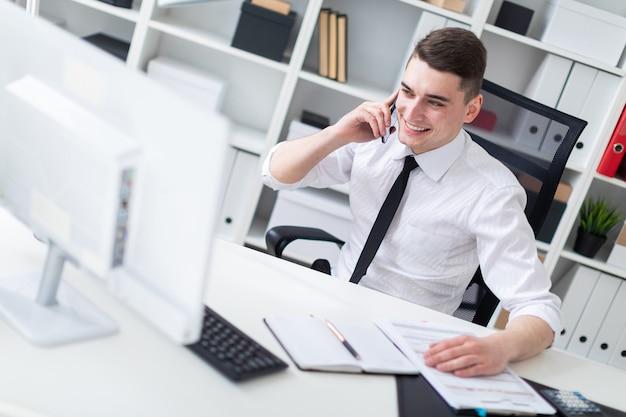 オフィスのコンピューター机に座って、モニターを見ている若い男。