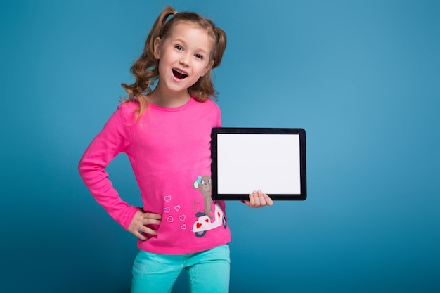猿と青いズボンとピンクのシャツで美しい少女は空のタブレットを保持します。