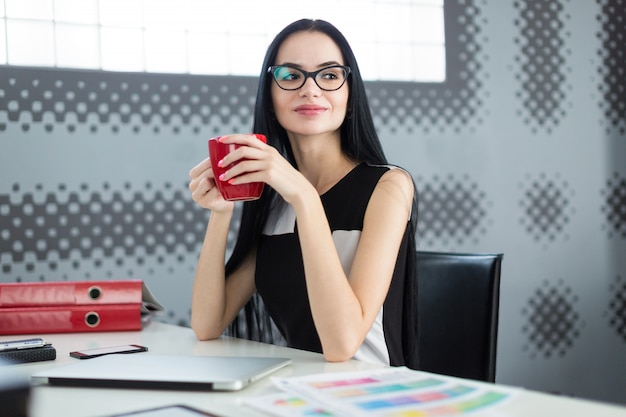 Милая, молодая бизнес-леди в черном платье и очках сидит за столом и держит красную чашку