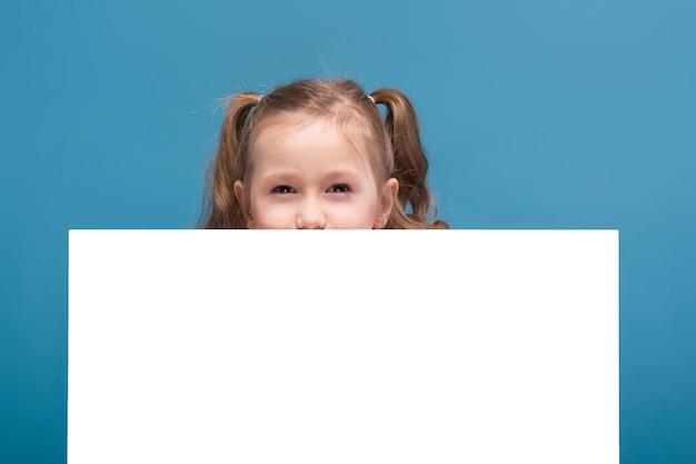 猿と青いズボンとピンクのシャツで魅力的なかわいい女の子は空のポスターを保持します。