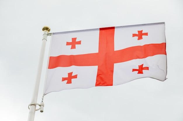 空に対して赤い十字架を持つジョージアの旗