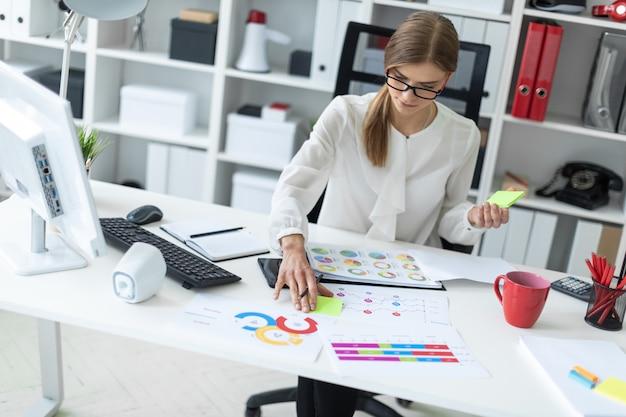 Молодая женщина сидит за столом в кабинете, держит в руке карандаш и клеит на наклейку лист.