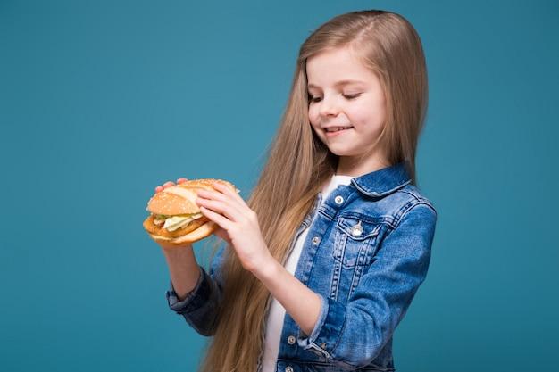 長い茶色の髪とジャンジャケットでかわいい女の子がハンバーガーを保持します。
