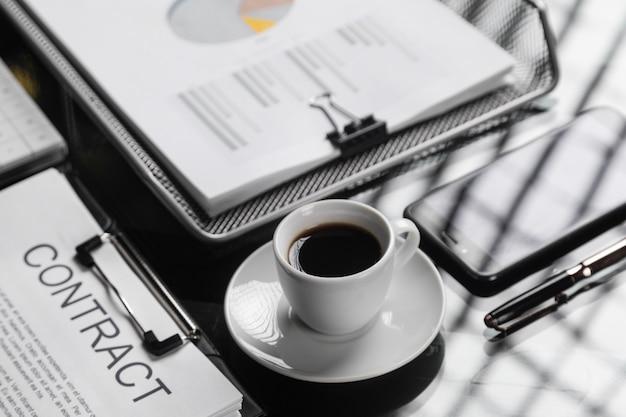 一杯のコーヒーのクローズアップの契約に署名する