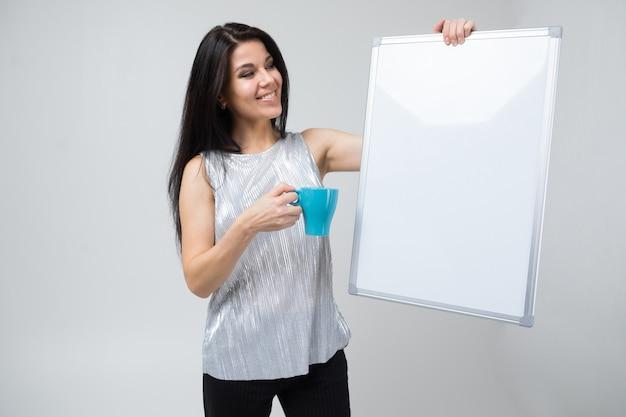 ターコイズブルーのカップと磁気ボードを持つ少女が孤立した光を立っています。