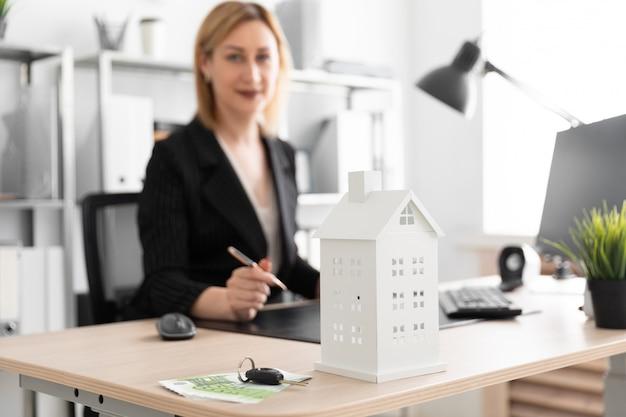 Фотография с глубиной резкости, выделенная направленность макета дома. молодая девушка работает в офисе.