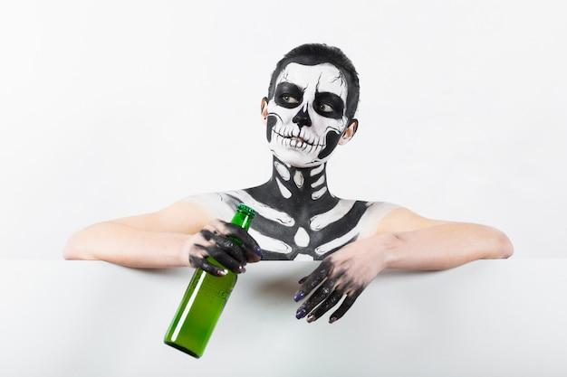 Привлекательная девушка со скелетом держит зеленую стеклянную бутылку