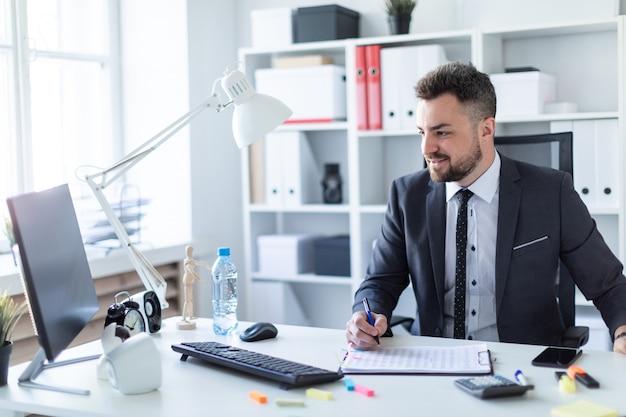 Мужчина сидит в кабинете за столом, держит ручку и работает с документами и компьютером.