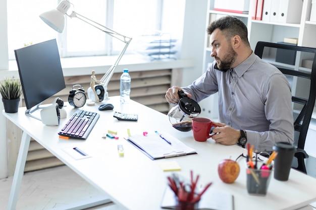 オフィスの若い男がテーブルに座っています