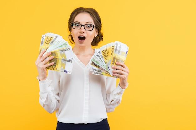 立っている彼女の手でお金で自信を持って美しい幸せな若いビジネス女性の肖像画
