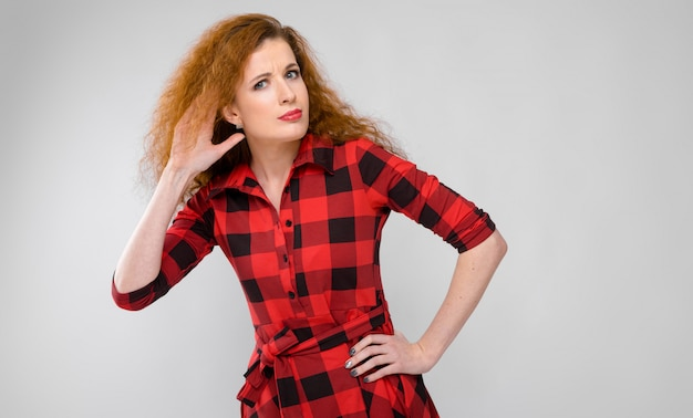 Молодая рыжеволосая женщина в красной клетчатой рубашке. молодая женщина приложила руку к уху