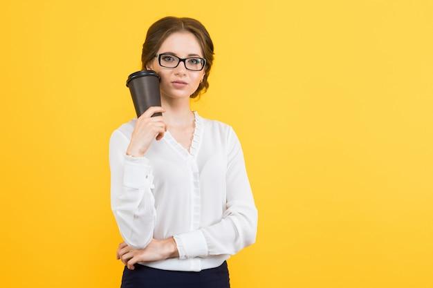 彼女の手でコーヒーカップを保持している自信を持って美しい若いエレガントなビジネス女性の肖像画