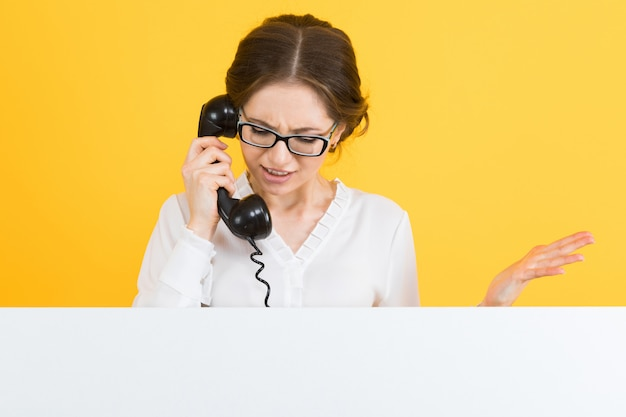 電話で自信を持って美しい怒っている若いビジネス女性の肖像画