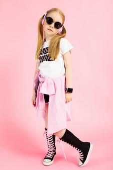 Портрет красивой девушки в шортах, футболке и высоких кроссовках.