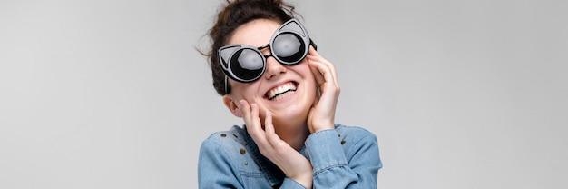 Молодая брюнетка женщина в черных очках. кошачьи очки. волосы собраны в пучок. женщина держит ее лицо.