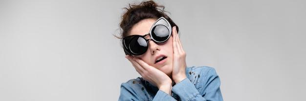 黒眼鏡の若いブルネットの女性。猫メガネ。髪はパンに集められます。女性は彼女の顔を持っています。