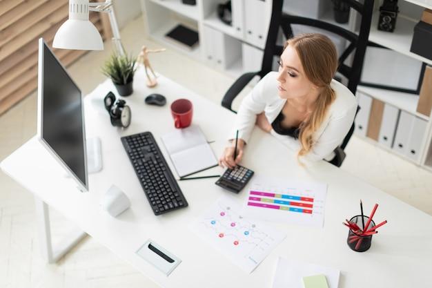 若い女性がオフィスのコンピューター机に座って電卓を頼りにしています。