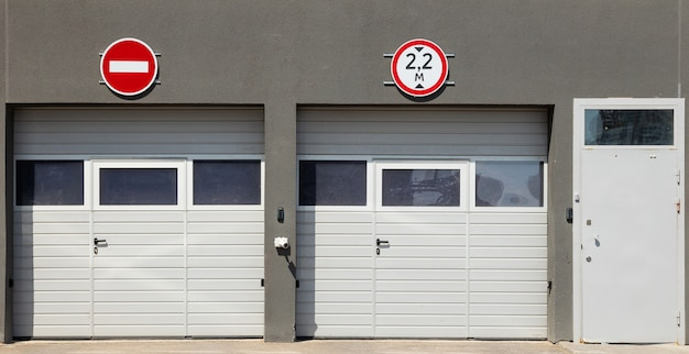 Вид спереди на два закрытых белых гаражных ворот и электронную входную дверь, серые карнизы и дорожные знаки на нем